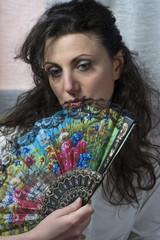 giovane donna nasconde il viso dietro un ventaglio colorato