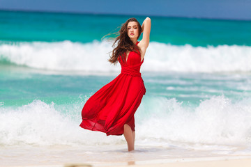 beautiful woman in a red dress  standing on the tropical sea coa