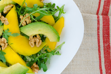 Salad with mango, avocado, rucola and walnuts