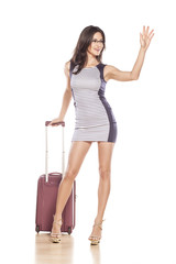 young pretty girl with suitcase waving hand