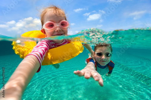 Kids having fun swimming on summer vacation - 64278602