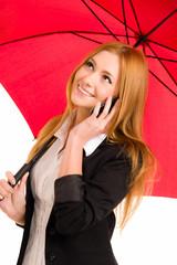 Hübsche junge Frau mit rotem Schirm telefoniert