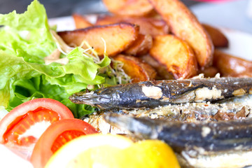 Grilled sardine fish served with green salad and potatoes