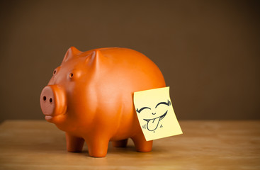 Post-it note with smiley face sticked on piggy bank