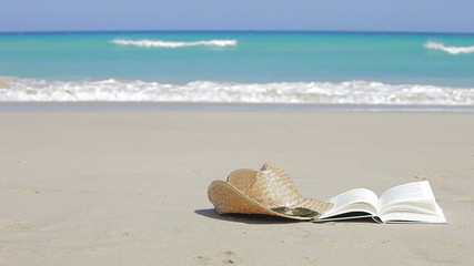 Book, sunglasses and straw hats on the beach. Relax concept