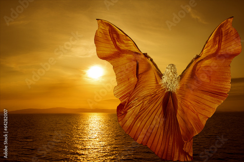 Woman with butterfly wings flying on fantasy sea sunset