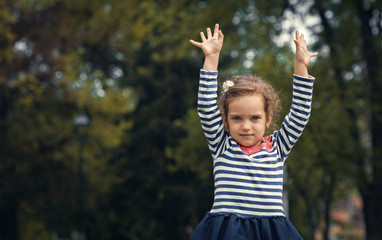 Playful little girl in park with open arms - outstretched