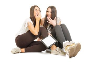 Two teenage girls with tablet having fun