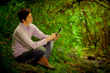 man using tablet in the forest