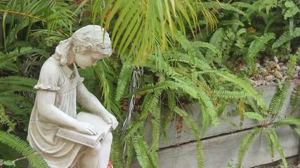 Statue of a little girl reading a book in a garden setting.