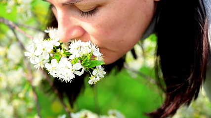 beautiful women smelling white flowers in springtime