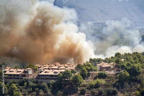 Fire burning mountain forest and village, danger for the houses - 64291472