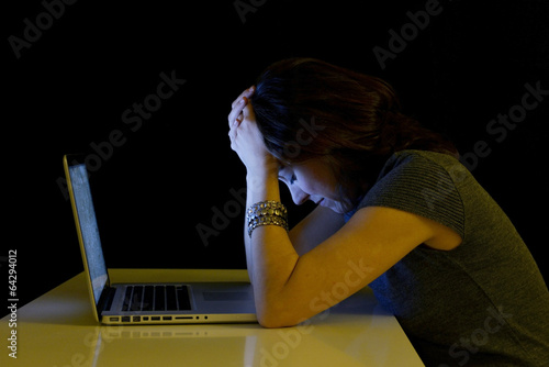 Young student woman alone  with computer crying sad depressed - 64294012