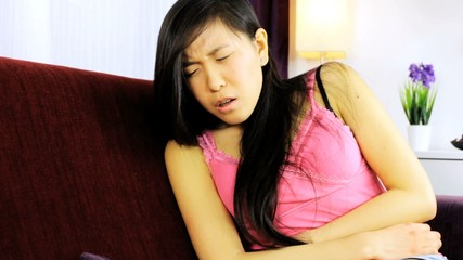 Sick asian american girl at home with stomach ache