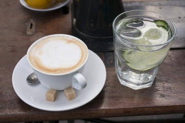 cappucinno and glass of water on wooden table