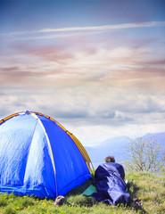 Man lie in sleeping bag near the tent