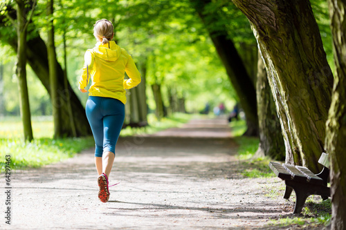 Leinwanddruck Bild Woman runner running jogging in summer park