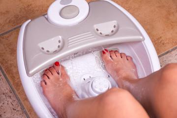 Woman's feet in a vibrating feet massager