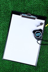 Sheet of paper, stopwatch and whistle on grass close-up