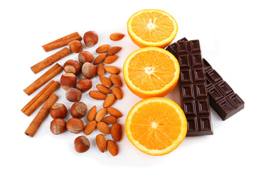 Chocolate, orange, nuts and cinnamon isolated on white