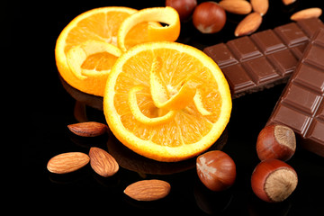 Chocolate, orange and nuts on black background