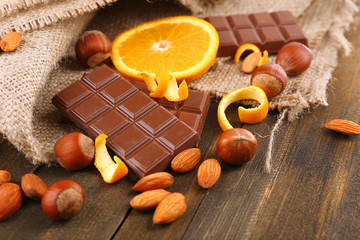 Chocolate, orange and nuts on wooden table