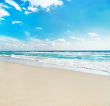 Fototapety sea beach against wave foam and blue sunny sky - vacation concep