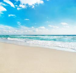 sea beach against wave foam and blue sunny sky - vacation concep