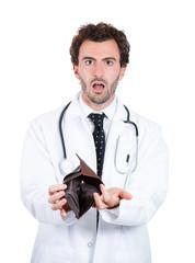 Closeup portrait Poor shocked doctor holding empty wallet