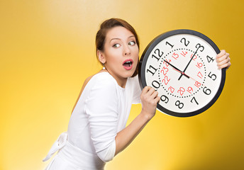 Running out of time. Girl holding wall clock, yellow background