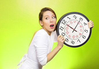 Businesswoman running out of time, holding wall clock