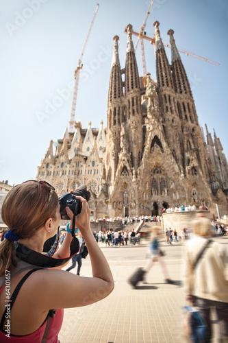 Zdjęcia na płótnie, fototapety, obrazy : Young woman taking picture of Sagrada Familia, Barcelona, Spain