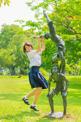 Cute Thai schoolgirl is jumping with a statue in the park