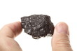 Coal lump carbon nugget in male hand isolated