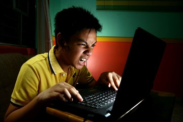 Asian Teen Playing or Working on a Laptop Computer