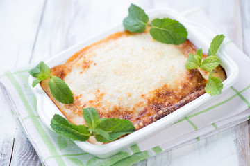 Vegetable lasagna with mint leaves over white wooden background