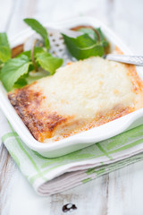 Vegetable lasagna in a glass dish, close-up, vertical shot