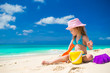 Adorable little girl playing on the beach with white sand
