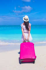 Back view of young beautiful woman with large suitcase on