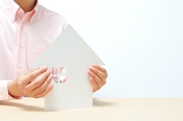 白い家を支えるピンクのシャツの男性