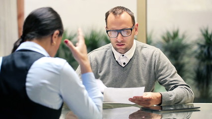 Unhappy businessman talking to candidate during job interview