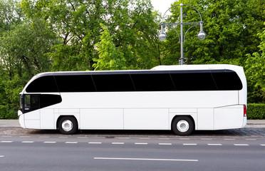 Weisser Reisebus mit getönten Scheiben vor Wald
