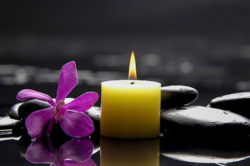 burning candles with orchid on blacks