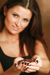 Female hands cupped holding coffee beans.
