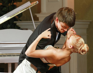 Bridal couple  dancing in front of a piano.