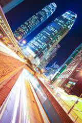 Road tunnels light trails on modern city buildings backgrounds i