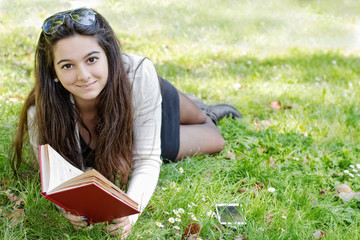 smiling girl with a book in outdoor scene