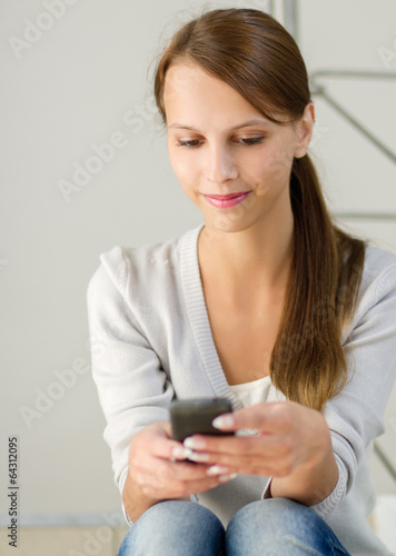 Pretty young woman holding a cell phone.