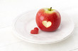 Apple with a heart shaped cut-out on a plate