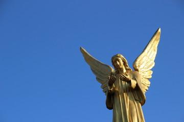 goldener Engel vor blauem Himmel